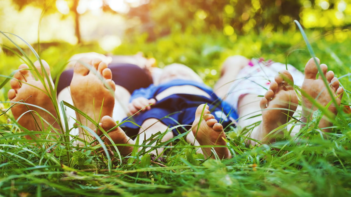 barefoot family laying in grass