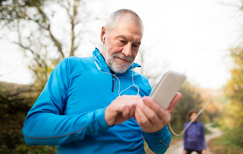 senior runner using headphones choosing song