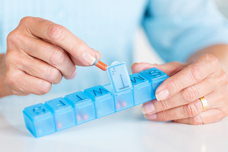woman hands placing pills in sorter